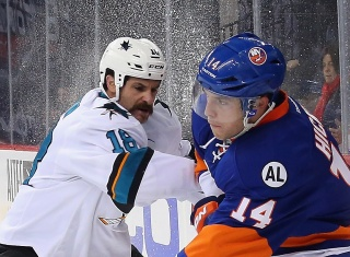 NEW YORK, NY - OCTOBER 17: Mike Brown #18 of the San Jose Sharks checsk Thomas Hickey #14 of the New York Islanders during the first period at the Barclays Center on October 17, 2015 in the Brooklyn borough of New York City. (Photo by Bruce Bennett/Getty Images)