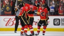 Sean Monahan #23, T.J. Brodie #7 and Johnny Gaudreau #13 of the Calgary Flames celebrate
