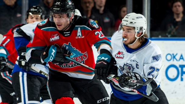 Matthew Wedman #20 of the Kelowna Rockets stick checks Phillip Schultz #27 of the Victoria Royals